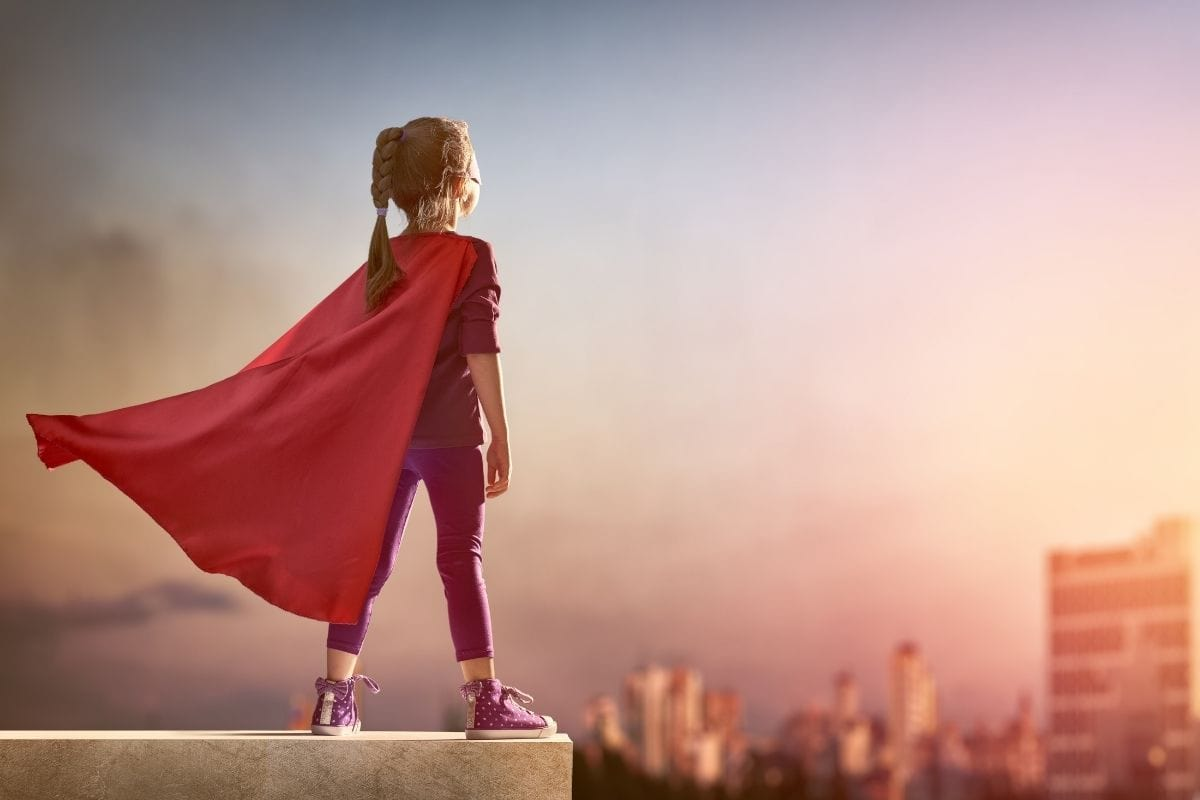 girl with cape stands on ledge showing girl power
