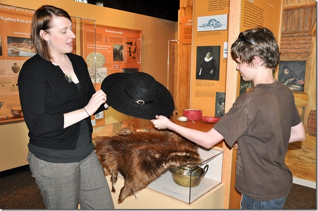 Anya Lee encourages boy to touch beaver hat and beaver pelt.