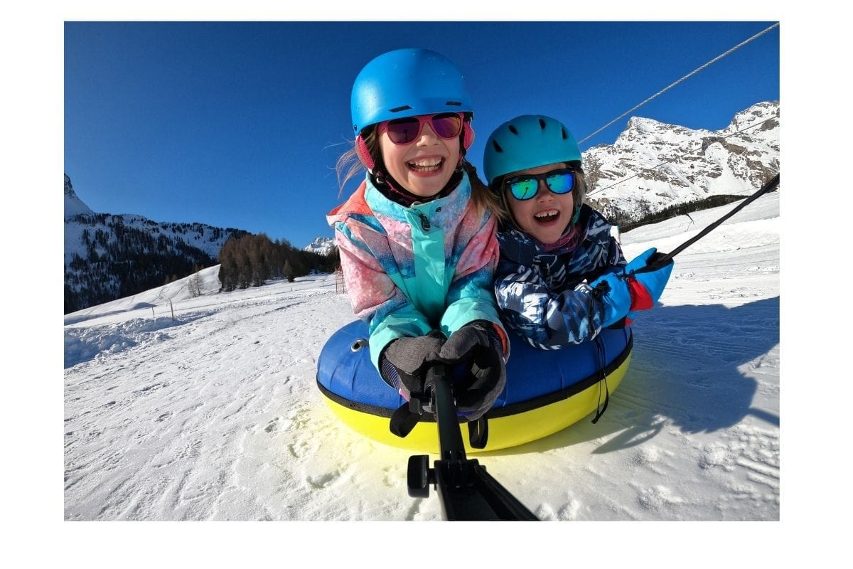 Two kids laughing on snow tube.