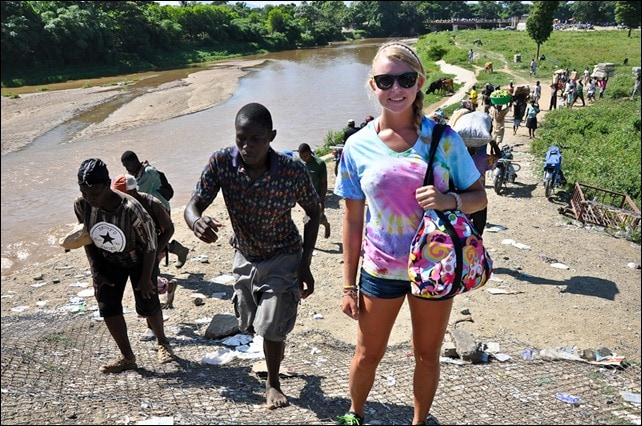 Family travel to Dajabon Market Haiti, teen poses in front of stream of Haitian carrying wares.