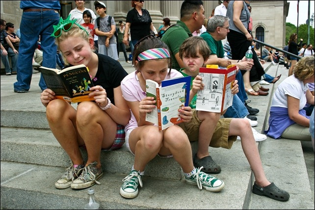 Kids reading about storybook travel on the Met steps in New York City.