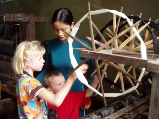 Kids are introduced to how silk is made, as the thread is spun onto a wheel.