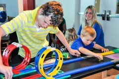 Teen and preschool cousins share an enriching moment, testing kinetic energy on the race tracks at the California Science Center.