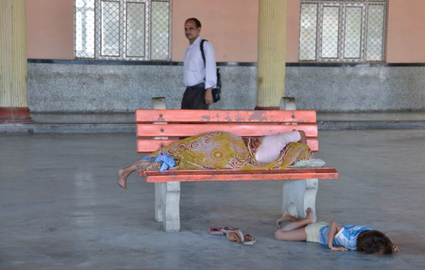 Mother and child, sleeping on bench and floor - Poverty in India - Delhi, India