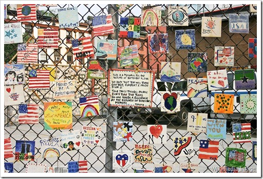 A small monument to the victims of the September 11th attacks on the fence of a car lot on Greenwich and Seventh Avenues in New York City.