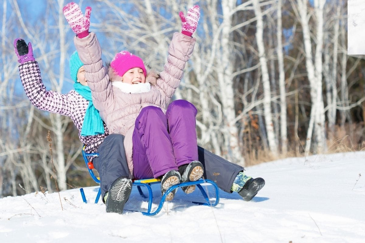 Kids enjoy winter fun sledding on snow covered hill.