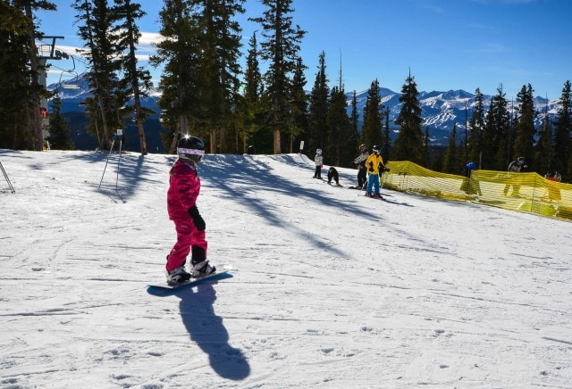 Young girl snowboarder, dressed all in pink, at Keystone in Colorado.