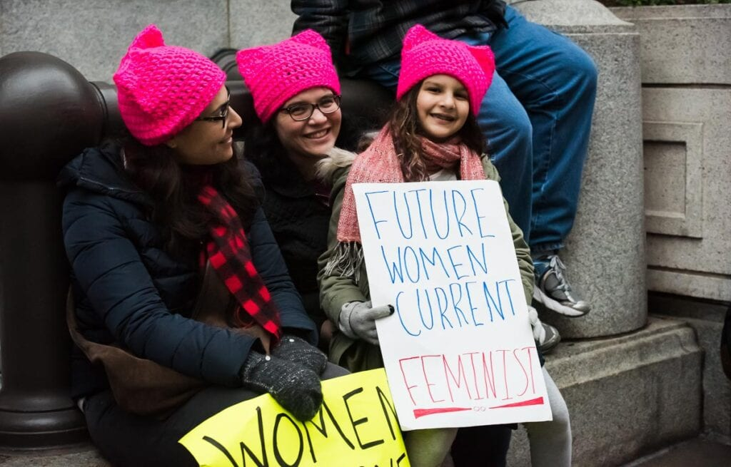 """Young girl holds up sign that says """"Future Woman, Current Feminist"""" at Women's Rights Protest in Washington DC in January 2017."""